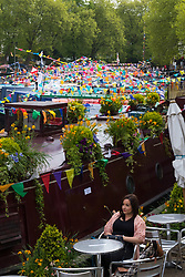 Little Venice, London, April 30th 2017. Narrowboaters from all over the UK gather for the annual Canalway Cavalcade, held on the May Day Bank holiday weekend, organised by the Inland Waterways Association, where boaters get the chance to display their immaculately prepared and brightly painted craft as well as compete in various manoeuvring tests. PICTURED: The hazy sunshine catches the colourful bunting on the moored narrowboats.<br /> Credit: ©Paul Davey<br /> To licence contact: <br /> Mobile: +44 (0) 7966 016 296<br /> Email: paul@pauldaveycreative.co.uk<br /> Twitter: @pauldaveycreate