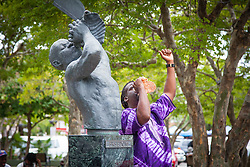 Jason Meade, Sr. blows the conch shell next to the Freedom Statue in Emancipation Garden between stops on the walking tour.  10th Annual Dollar Fo' Dollar Culture & History Tour commemorating the anniversary of the successful protest  demanding better pay by Queen Coziah and the 19th century coal laborers in the streets of downtown Charlotte Amalie.  12 September 2015.  St. Thomas, VI.  © Aisha-Zakiya Boyd