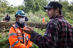 Denham, UK. 29th September, 2020. A security guard working on behalf of HS2 Ltd blocks an environmental activist objecting to the felling of trees in Denham Country Park for works connected to the HS2 high-speed rail link. Anti-HS2 activists based at the nearby Denham Ford Protection Camp and protesting against the destruction of the woodland contend that the area of Denham Country Park currently being felled is not indicated for felling on documentation supplied by HS2 Ltd.
