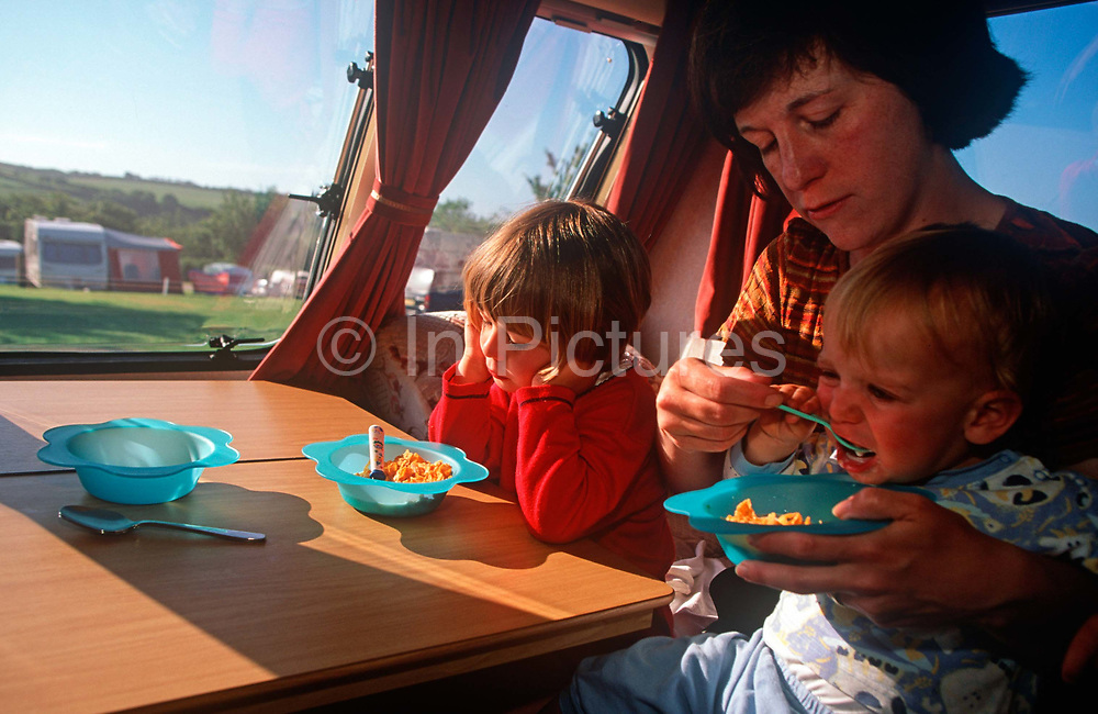 A mother feeds her small child alongside his older sister in a  1990s-era caravan while holidaying on a camping site in Cornwall, on 13th August 2000, in Looe, England.
