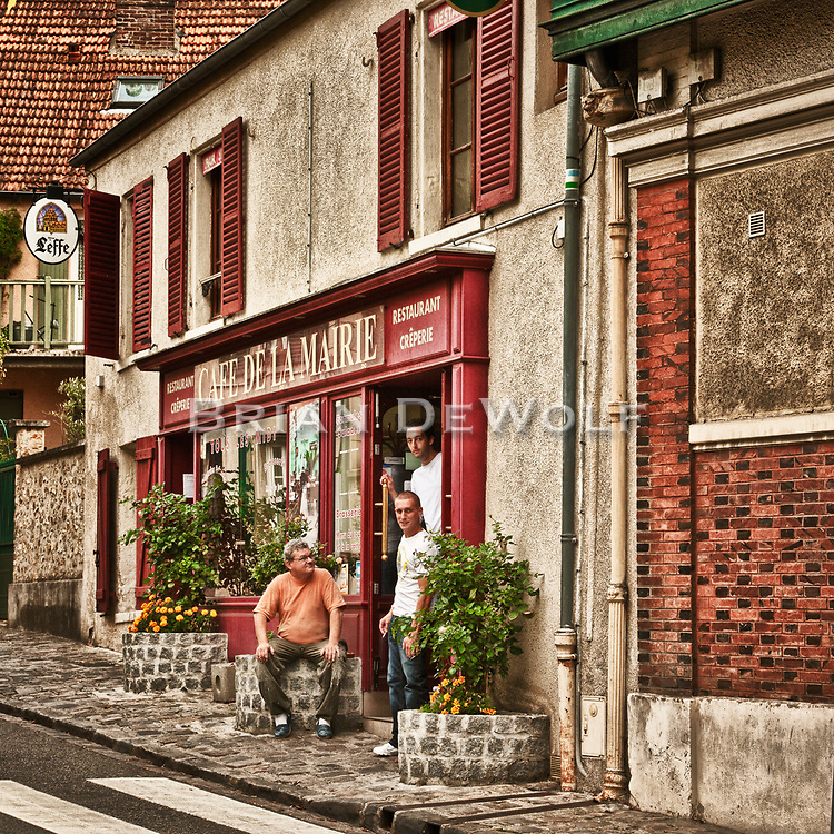 Patrons in the doorway of a cafe in Louveciennes, France.  Aspect Ratio 1w x 1h.
