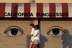 two women, caucasian & afro african american pass store front in Califronia.