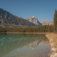 A photographer stands beside Waterfowl Lake in Banff National Park, Alberta, Canada.
