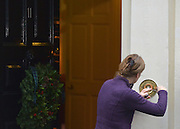 © Licensed to London News Pictures. 05/12/2012. Westminster, UK A woman repairs the doorbell at number 11 Downing Street today. British Chancellor of the Exchequer George Osborne on Downing Street today, 5th December 2012, prior to giving his Autumn Statement to the House of Commons on the UK economy. Photo credit : Stephen Simpson/LNP