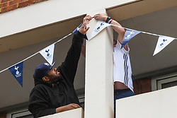 Two men put up bunting in a block of flats opposite Spurs' stadium ahead of Tottenham's Champions League final with Liverpool to be played at Atletico Madrid's Wanda Metropolitano Stadium in Madrid. Tottenham, London, May 29 2019.