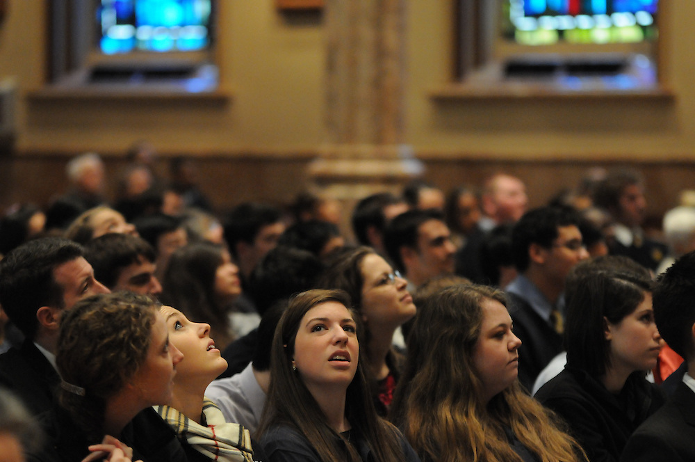 """Catholic high schools students peer at the ornate ceiling of Holy Name Cathedral as Chicago Archbishop Francis Cardinal George details the building's history during a mass promoting service leadership in the church under the theme """"A Call To Serve""""."""
