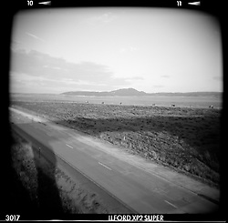 """Bikes Across the Plains. I-90, WY. 1999<br /> <br /> Limited Edition Print from an edition of 50. Photo ©1999 Michael Lichter<br /> <br /> The Story: The plains glisten in the bright western sun while bikes and a dotted line converge in the distance.  A """"Stonehenge"""" like shadow from the overpass marks the land."""