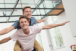 Homosexual couple giving piggyback ride, smiling
