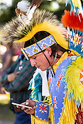 A Native American dancer from the Arapahoe people dressed in traditional costume checks his iPhone at the Indian Village during Cheyenne Frontier Days July 25, 2015 in Cheyenne, Wyoming. Frontier Days celebrates the cowboy traditions of the west with a rodeo, parade and fair.