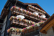 Multi-colored flower boxes on old wood buildings. Zermatt, in the Pennine Alps, Switzerland, Europe.