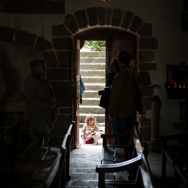 A little girl kneels and pets a puppy at the doorway to the parish church of Saint Pierre on Mont Saint Michel, in Lower Normandy, France. Adult tourists are in the shadows.