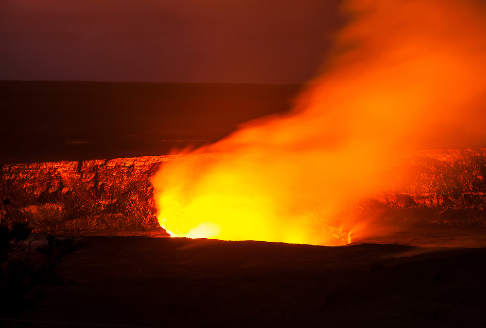 Kilauea Caldera glowing with billowing and rising gases and steam from the lava lake inside as seen from the visitors center, Hawaii Volcanoes National Park, Hawai'i, USA.