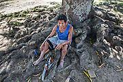 A craftsman from Annai (North Rupununi) is sitting under a huge local tree.