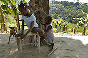 Children waste the day away in the back yard of their families home up on the mountain above Carrefour, Haiti.  The small farm in the background barely produces enough vegetables for the family to eat.  These children are not able to find a sponsor family for their schooling so they spend their days at home.