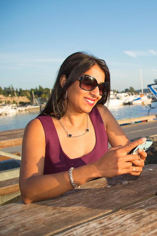 North America, United States, Washington, Kirkland, woman with cell phone near dock at Marina Park.  MR