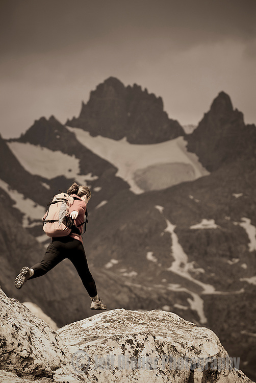 A young woman jumps over rocks while hiking in Titcomb Basin, Wind River Mountains, Wyoming.