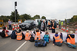Enfield, UK. 15th September, 2021. A motorist films Insulate Britain climate activists blocking a slip road from the M25 at Junction 25 as part of a campaign intended to push the UK government to make significant legislative change to start lowering emissions. The activists, who wrote to Prime Minister Boris Johnson on 13th August, are demanding that the government immediately promises both to fully fund and ensure the insulation of all social housing in Britain by 2025 and to produce within four months a legally binding national plan to fully fund and ensure the full low-energy and low-carbon whole-house retrofit, with no externalised costs, of all homes in Britain by 2030 as part of a just transition to full decarbonisation of all parts of society and the economy.