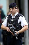 Armed policeman wearing flak jacket and with machine gun, London, England, UK
