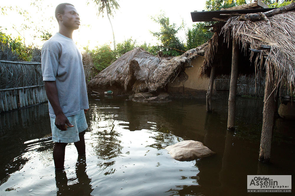 A man stands in floodwater next to a partially collapsed home in the village of Avedji, Benin on Monday October 25, 2010.