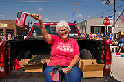 03 JULY 2021 - NORWALK, IOWA: A woman gives out American flags during the 4th of July parade in Norwalk, Iowa. Last year's parade was cancelled because of the COVID-19 pandemic. Norwalk is an agricultural community south of Des Moines. In recent years, Norwalk has become a suburb of Des Moines.        PHOTO BY JACK KURTZ