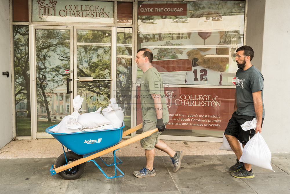 Workers carry sand bags to prevent flooding in the historic King Street shopping district in preparation for approaching Hurricane Florence September 11, 2018 in Charleston, South Carolina. Florence, a category 4 storm, is expected to hit the coast between South and North Carolina and could be the strongest storm on record for the East Coast of the United States.