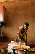 Woman pouring coffee from a jebena in preparation for a taditional coffee ceremony, Lalibela, Ethiopia