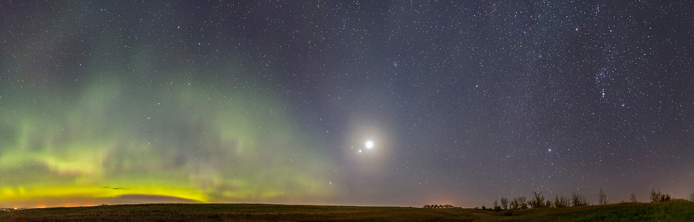 A panorama of the pre-dawn sky on October 8, 2015, with a sky full of wonders:<br /> • the Northern Lights, or aurora<br /> • The Big Dipper above the aurora, somewhat distorted by the panorama projection<br /> • at centre, a conjunction and line-up of planets, with from bottom to top: Jupiter, Mars and Venus, with the bright waning crescent Moon beside Venus at top, and also beside the star Regulus in Leo<br /> • The Beehive star cluster well above the planet grouping<br /> • Orion and Canis Major in the winter sky at right with the Milky Way.<br /> <br /> I shot this from home, using the Canon 6D and 24mm lens on a fixed tripoid (no tracking), for 7 segments, each a 30-second exposure at f/2.2 and at ISO 1250. Stitched in Photoshop.