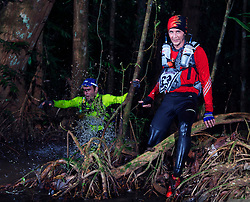 """© Licensed to London News Pictures. 11/10/2013. BRAZIL.  Two athletes racing through dark swamps in the heart of the amazon jungle. Competitors take part in the Jungle Marathon 2013, the """"The toughest ultra marathon in the world"""" The race is 245 km long through the biggest jungle in the world, The Amazon. It attracts competitors from all countries world wide. Competitors run through territories of indigenous tribes throughout the 7 day race, where they stay with them as guests.. Photo credit : Alexander Beer/LNP"""
