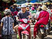 """14 FEBRUARY 2019 - SIHANOUKVILLE, CAMBODIA: A Chinese worker rides his motorcycle through the Leu Market in Sihanoukville. There are thousands of Chinese workers in Sihanoukville who work to support the casino and hotel industry in the town. There are about 80 Chinese casinos and resort hotels open in Sihanoukville and dozens more under construction. The casinos are changing the city, once a sleepy port on Southeast Asia's """"backpacker trail"""" into a booming city. The change is coming with a cost though. Many Cambodian residents of Sihanoukville  have lost their homes to make way for the casinos and the jobs are going to Chinese workers, brought in to build casinos and work in the casinos.      PHOTO BY JACK KURTZ"""
