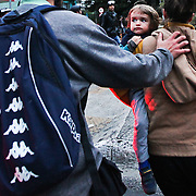 A child is guided out of danger as rocks fly when protesters affiliated with the Black Bloc anarchist group throw rocks at banks and other shops during a protest aimed at lowering metro fares in Sao Paulo on Thursday, June 19, 2014. Credit: Byron Smith