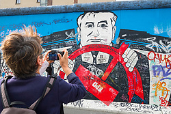 Tourist taking photograph of mural painted on original section of Berlin Wall at East Side gallery in Berlin, Germany ...Editorial Use Only