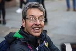 London, UK. 16 October, 2019. Guardian journalist and environmental campaigner George Monbiot sits on the pavement in Whitehall after having been arrested by Metropolitan Police officers under Section 14 of the Public Order Act 1986 during an Extinction Rebellion right to protest demonstration.
