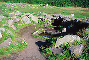 Prehistoric buildings at Drombeg henge site, County Cork, Ireland. The stone trough of water is thought to have been associated with cooking suggesting that this building was a kitchen of some sort.