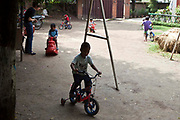 Young Nepalese boys play outdoors on bikes and tricycles in the MSPN garden in Kathmandu, Nepal.  The MSPN centre is run by 'Friends of Needy Children' and is a residential care centre for children who are infected with HIV/AIDS.  In addition to medical and psychological support, they are encouraged to play with other children.