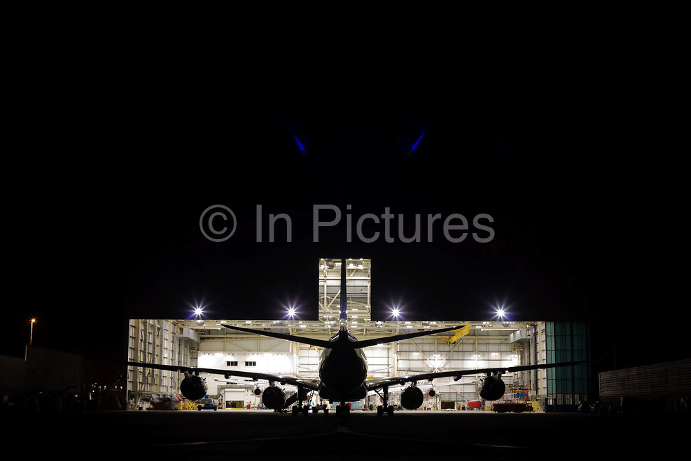 """In the darkness of a taxiway at the southern end of Heathrow Airport, the bright lights of an engineering hangar spill out into the night. A Boeing 747 Jumbo jet sits nose-in behind another during a scheduled set of maintenance tasks that every aircraft needs to keep to in order for its continued airworthiness. The unmistakable shape of this large aircraft is a half-silhouette against the intensity of the hangar and blue flare spots that arise from the internal glass in the camera's lens. From writer Alain de Botton's book project """"A Week at the Airport: A Heathrow Diary"""" (2009)."""