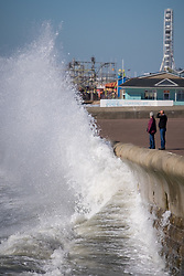 © Licensed to London News Pictures. 05/10/2016. Portsmouth, Hampshire, UK.  People observe the unsettled sea in the windy weather as waves crash against the seafront in Southsea this afternoon, 5th October 2016. Today is another dry and sunny, but very windy autumn day on the south coast of England. Photo credit: Rob Arnold/LNP