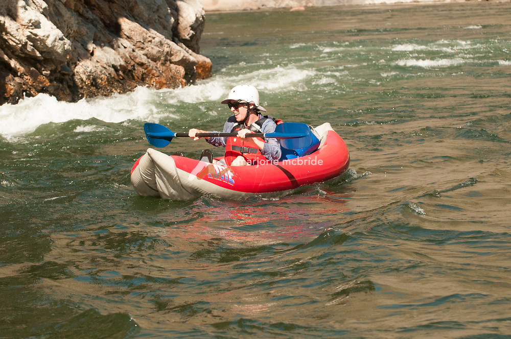 Kayaking and enjoying whitewater at Cliff side rapid in the Impassible Canyon on the Middle Fork of the Salmon River during six day rafting vacation, Idaho.