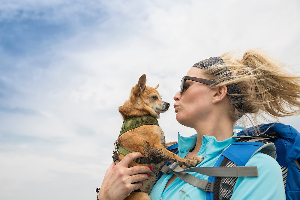 Lifestyle image of a Woman kissing Chihuahua