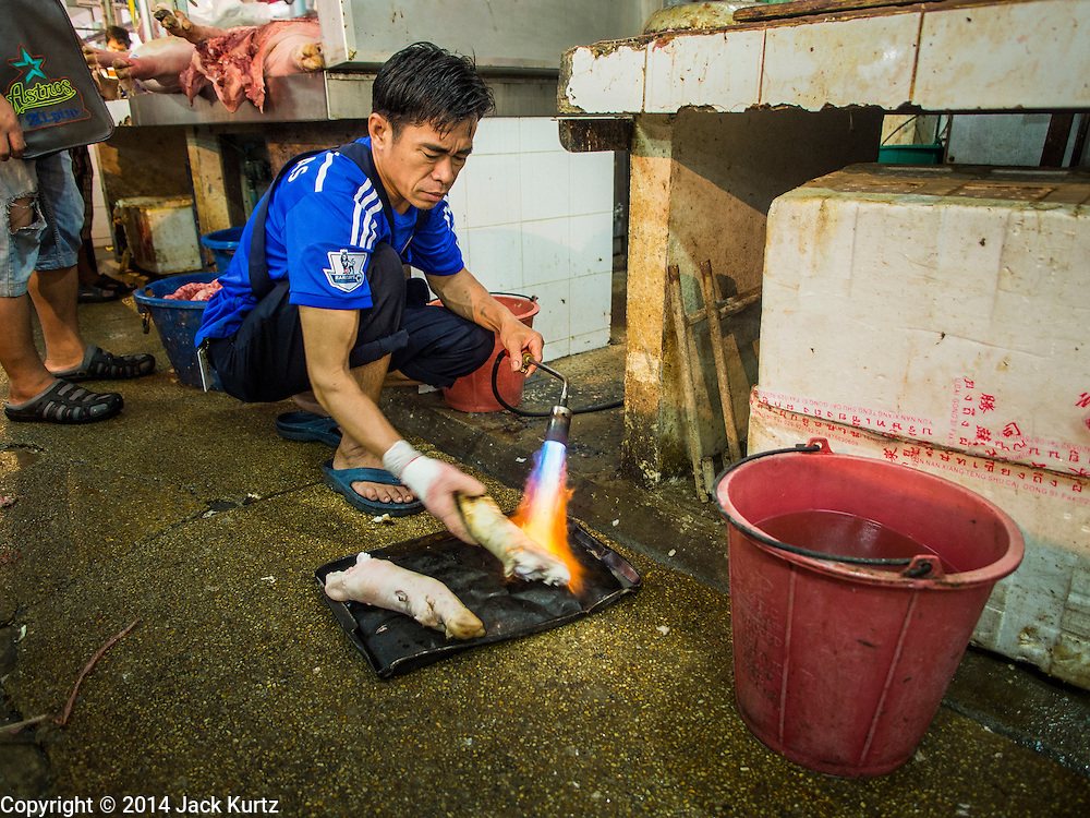 19 NOVEMBER 2014 - BANGKOK, THAILAND: A vendor burns the hair off of a pig's foot in Khlong Toei Market in Bangkok. Between July and September the economy expanded 0.6 percent compared to the previous year, the National Economic and Social Development Board (NESDB) reported. Thailand's economy achieved a weak 0.2 per cent growth across the first nine months of the year. The NESDB said the Thai economy is expected to grow by 1 percent in 2014. Authorities say the sluggish growth is because tourists have not returned to Thailand in the wake of the coup in May, 2014, and that reduced demand for computer components, specifically hard drives, was also hurting the economy. Thailand is the leading manufacturer of computer hard drives in the world. The Thai government has announced a stimulus package worth $11 billion (US) to provide cash handouts to farmers and promised to speed up budget spending to boost consumption.   PHOTO BY JACK KURTZ
