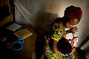 Mapendo Sakina, 20, is a teacher's assistant who is also a high school student in Kichanga, breast-feeds her one-year-old son, Fiston, who was born out of rape. According to her, she was raped by two Rwandan rebels in 2007. She also gave a birth to a boy, and once disowned by her father. Now back home, her parents finally accepted her and her child as members of family. She wants to be a math teacher.