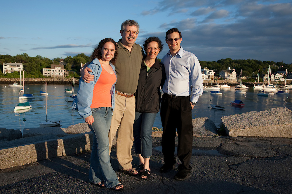North America, United States, Massachusetts, Rockport, family near sailboats in cove under dramatic clouds