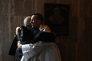 """Marist Catholic High School Senior Joe Ward (r) receives a congratulatory hug from an attendee of a recently-ended mass at Holy Name Cathedral that Ward conceived for Catholic high schools in the diocese of Chicago, Joliet, and Rockford. Chicago Archbishop Francis Cardinal George lead the mass celebration dedicated to the theme """"A Call To Serve""""."""