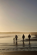 A family walks along the beach at sunset in Crescent City, California