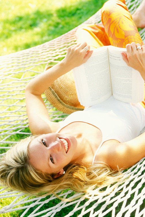 Portrait of a young woman relaxing on a hammock reading a book.