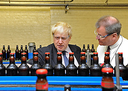 © licensed to London News Pictures. LONDON, UK.  02/06/11. Boris Johnson pulls a pint of London Pride at Fuller's Brewery today. The Mayor of London Boris Johnson visits two major manufacturing firms today, 02 June 2011, to see the role they play in supporting London's economy and why the UK's capital city  is so critical to their continued success. He called in to Fuller's in Chiswick, London's only traditional family brewery, to see their new multi-million pound brewing facility. He went on to visit Brompton bike factory. Where he met Brompton inventor Andrew Ritchie, who still owns the famous company and remains its Technical Director.  Photo credit should read Stephen Simpson/LNP