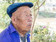 portrait of a Local mature man smoking at a small village in the mountains near Kumming, Yunnan province in southwest China in September