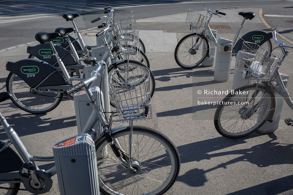 Rental bike docks on Dunajska Cesta (street) in the Slovenian capital, Ljubljana, on 27th June 2018, in Ljubljana, Slovenia. Ljubljana is a small city with flat terrain and a good cycling infrastructure. It was featured at eighth on the 'Copenhagenize' index listing the most bike-friendly cities in the world. A new bike counter on Dunajska Street declares publicly that there are many days with more than 5,000 cyclists who take a trip through there.