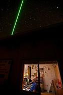 A scientist operates a green LIDAR laser at the Mauna Loa Observatory, Hilo, Hawaii.