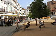 People sitting on benches in Plaza Mayor, Carceres, Extremadura, Spain