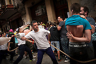 A boy tries to cover his back from the hits of the participants in the dance, while his friend rises his t-shirt. Hernani (Basque Country) 26 June 2013. This is part of the traditional 'dance of the fox' in St. Johnn's festival. A group of strong people goes out headed by 'the fox', holding a robe and with cow's bladders in the other hand, surrounding and beating the people they find on the streets (Gari Garaialde/Bostok Photo)
